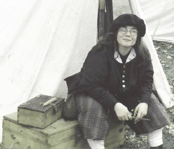 This is a picture of me, sitting on a wooden trunk at a Rendezvous event in Winona, Minnesota. I am in my 17th century soldiers uniform consisting of a Blue bonnet (sort of looks like a beret), Grey coat, plaid britches, wool socks and latchet shoes.